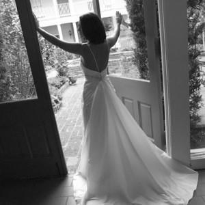 GIRL IN WEDDING DRESS LOOKING OUT WINDOW